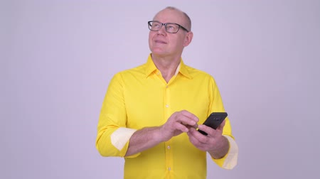 fince : Happy senior businessman thinking while using phone