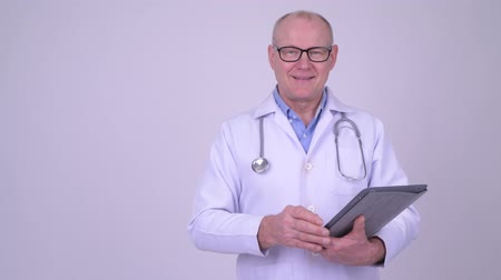 finnish : Happy senior man doctor using digital tablet and showing something