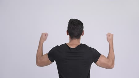 raising fist : Rear view of young multi-ethnic man cheering with fists raised Stock Footage