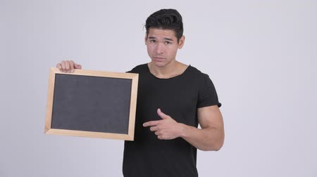 errado : Young stressed multi-ethnic man holding blackboard and giving thumbs down Stock Footage