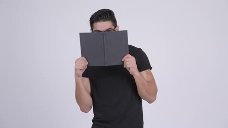 shy : Young multi-ethnic nerd man covering face with book
