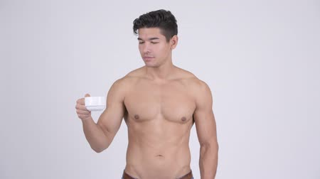 abs : Happy young handsome muscular shirtless man holding coffee cup and giving thumbs up
