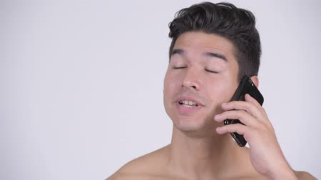 vlogging : Face of happy young shirtless muscular man talking on the phone Stock Footage