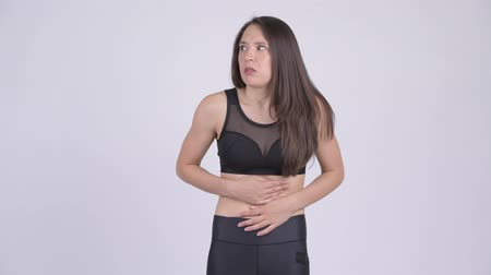 painéis : Young stressed multi-ethnic woman having stomach ache ready for gym Stock Footage