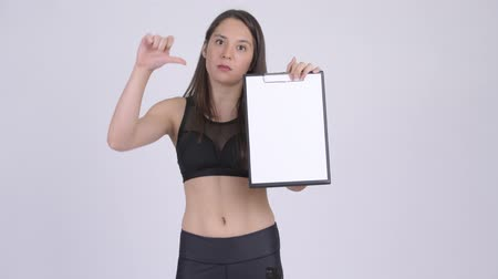 разочарование : Young upset woman showing clipboard and giving thumbs down ready for gym Стоковые видеозаписи