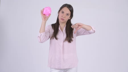 refusing : Young stressed multi-ethnic businesswoman holding piggy bank and giving thumbs down Stock Footage