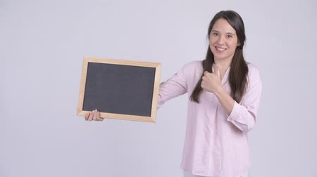 schválení : Young happy businesswoman holding blackboard and giving thumbs up