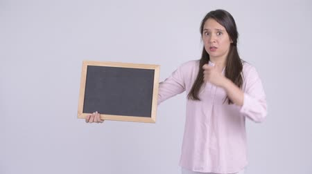 refusing : Young multi-ethnic businesswoman holding blackboard and giving thumbs down