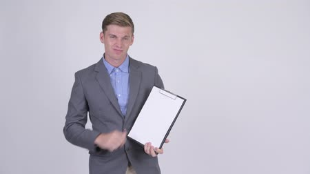 неправильно : Stressed young businessman showing clipboard and giving thumbs down Стоковые видеозаписи