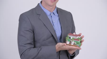 реальный : Happy young handsome businessman holding house figurine