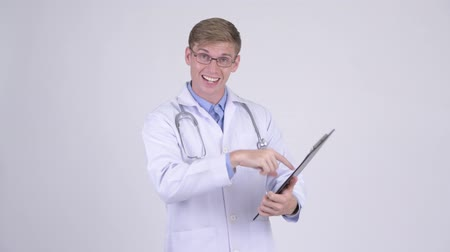 tło : Stressed young man doctor talking while reading on clipboard