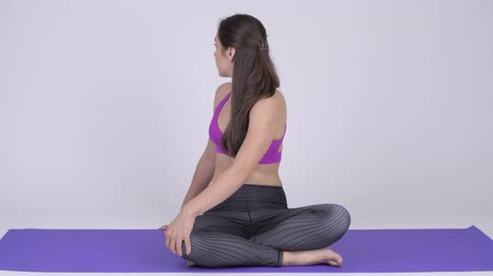 アーサナ : Young beautiful multi-ethnic woman doing Seated Twist yoga pose