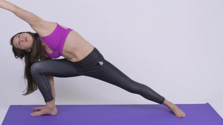 tilt down : Young beautiful multi-ethnic woman doing Extended Side Angle yoga pose Stock Footage