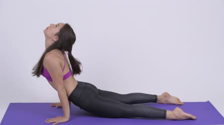 tilt down : Young beautiful multi-ethnic woman doing Downward Dog yoga pose Stock Footage