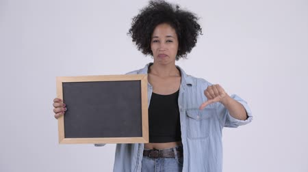 errado : Young stressed African woman holding blackboard and giving thumbs down