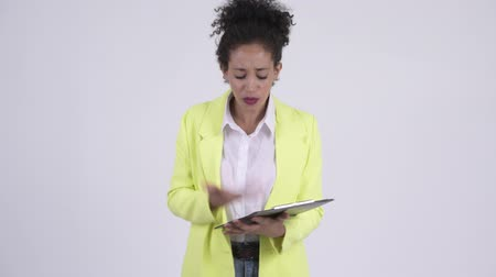 aborrecido : Young angry African businesswoman talking while holding clipboard Stock Footage