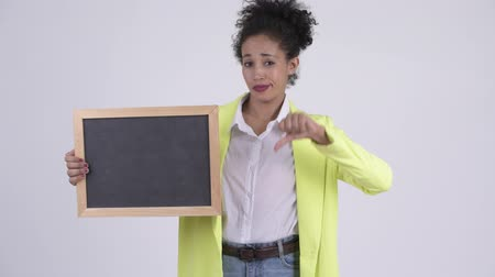 negative : Young stressed African businesswoman holding blackboard and giving thumbs down