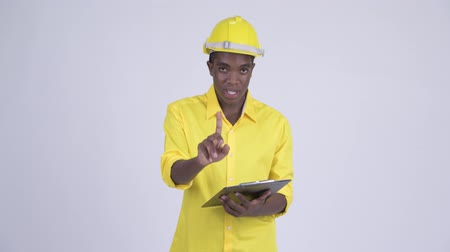 directing : Young African businessman as engineer talking while reading on clipboard