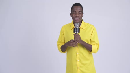 evsahibi : Young happy African businessman as host using microphone