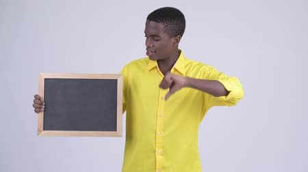 неправильно : Young stressed African businessman holding blackboard and giving thumbs down