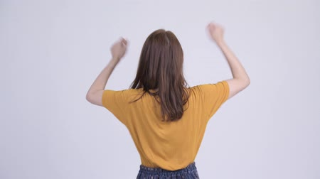 raising fist : Rear view of happy young beautiful Asian woman with fists raised Stock Footage