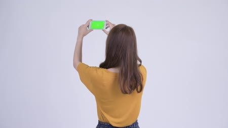 vlogging : Rear view of young Asian woman taking picture with phone