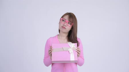 sudeste : Young happy Asian nerd woman thinking while holding gift box