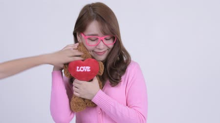 éretlen : Face of young happy Asian nerd woman holding teddy bear and acting childlike Stock mozgókép