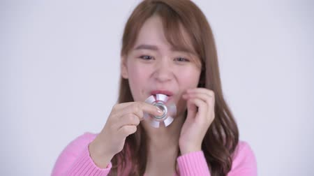 fad : Face of young happy Asian nerd woman playing with fidget spinner