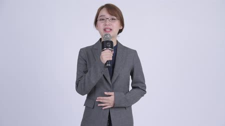 evsahibi : Young Asian businesswoman as newscaster using microphone