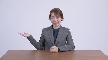 átnyújtás : Young happy Asian businesswoman presenting something at desk