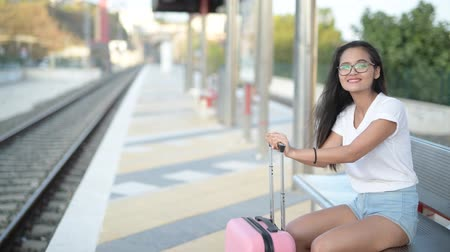durulması : Young Happy Asian Tourist Woman Sitting While Waiting For The Train Stok Video