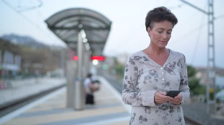 vlogging : Mature Beautiful Tourist Woman Using Phone While Waiting At The Train Station Stock Footage