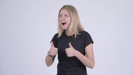 kciuk w górę : Young happy blonde woman looking excited while giving thumbs up Wideo