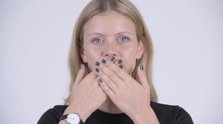 cubreboca : Face of young beautiful blonde woman covering mouth as three wise monkeys concept Archivo de Video
