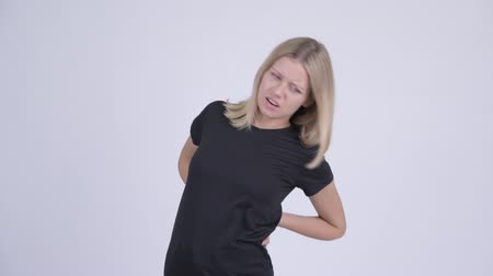 mal di schiena : Young stressed blonde woman having back pain Filmati Stock
