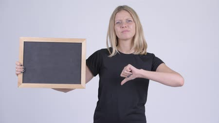 refusing : Young serious blonde woman holding blackboard and giving thumbs down Stock Footage