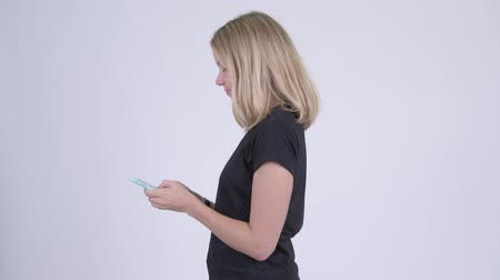 taken : Profile view of young blonde woman with phone being taken away Stock Footage
