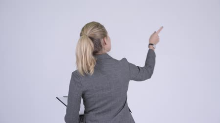 direto : Rear view of young blonde businesswoman directing and pointing finger