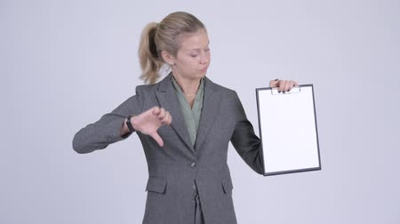 refusing : Young serious blonde businesswoman showing clipboard and giving thumbs down