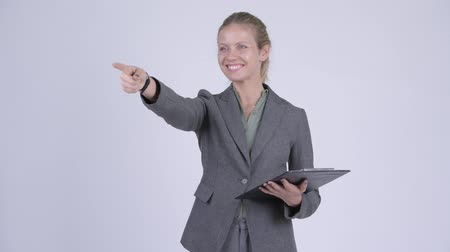 direto : Young happy blonde businesswoman directing while holding clipboard