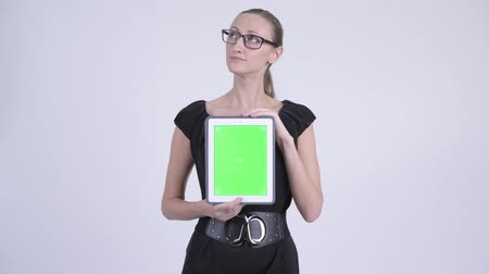 cópia : Happy blonde businesswoman thinking while showing digital tablet