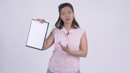 разочарование : Young serious Asian businesswoman showing clipboard and giving thumbs down