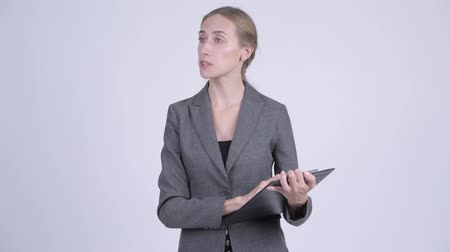 directing : Young blonde businesswoman directing while holding clipboard Stock Footage