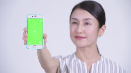 focus on foreground : Face of happy beautiful Asian businesswoman showing phone Stock Footage