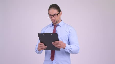 directing : Angry businessman talking while reading on clipboard