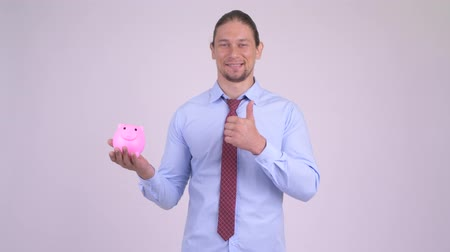 piggy bank : Happy handsome businessman holding piggy bank and giving thumbs up Stock Footage