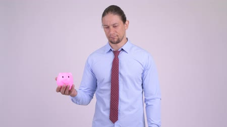 quebrado : Stressed businessman holding piggy bank and giving thumbs down Vídeos
