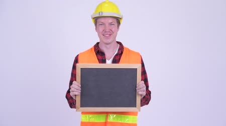 finnish : Happy young man construction worker holding blackboard