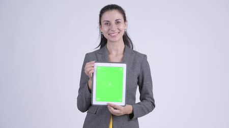egyenes haj : Happy young beautiful businesswoman thinking while showing digital tablet